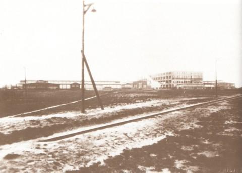 Bouw van de Philips fabriek in 1929. Links is men reeds gestart met de productie van transformatoren en spoelen in houten loodsen. Rechts de eerste verdiepingen van de hoogbouw in opbouw. Dwars over het plein heeft men een stoomtramlijn aangelegd voor de aanvoer van bouwmaterialen.
