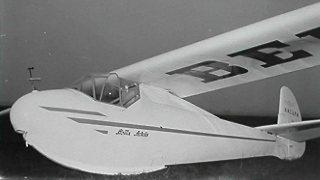 """De Rhönbussard van ANCUPA. Bemerk het ANCUPA logo op de staart, de """"Belga"""" publiciteit op de vleugel, en de vermelding """"Stella Artois"""" op de romp."""